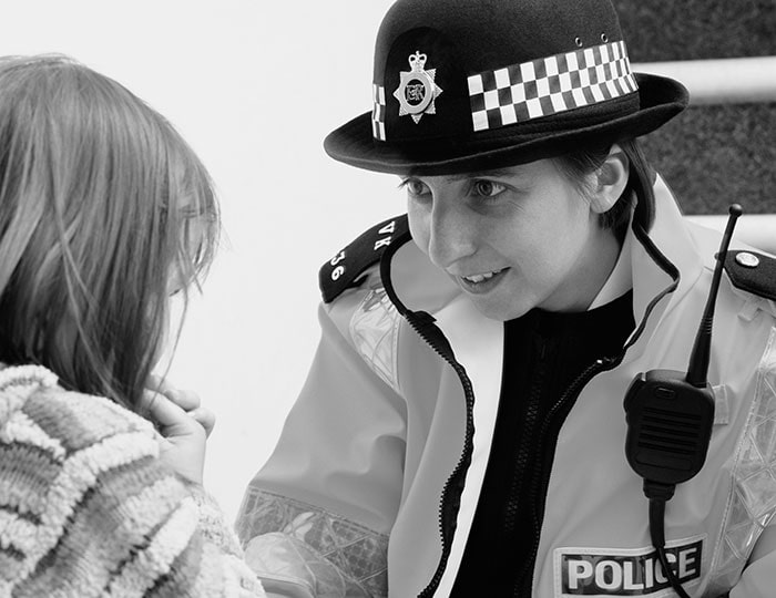Policewoman talking to girl in community