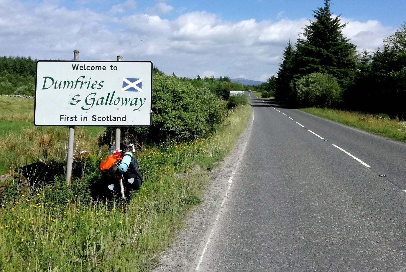 Photo of a road with sign for D&G with camping backpack resting at its foot on a sunny day